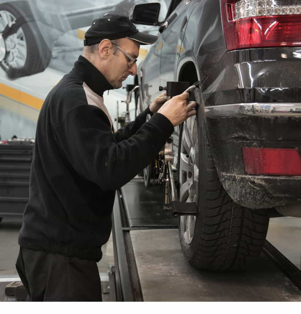 Man Adjusting Wheel Alignment
